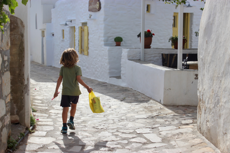 child running on greek street