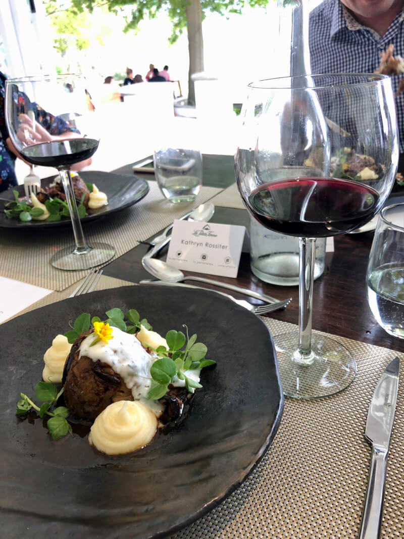 A glass of red wine with signature lamb dish